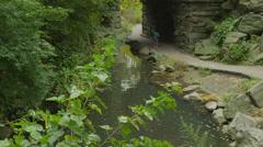 Wide shot of tourist walking under park bridge / New York, New York, United Stock Footage