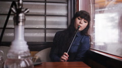 Beautiful young woman inhaling hookah. girl smoking shisha in cafe - stock footage
