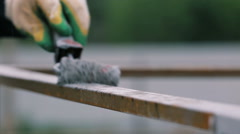 Worker painting the fence using a paint roller Stock Footage