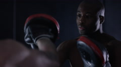 4K Muscular MMA fighter training with partner in dark environment - stock footage