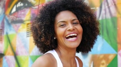 Young Afro Brazilian woman smiling on colorful background - stock footage