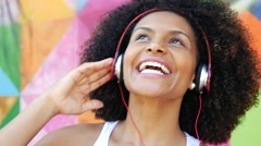 Stock Video Footage of Brazilian afro woman listing to music on colorful background