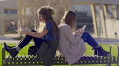 Teens Sit Back To Back On A Park Bench And Check Their Smartphones Stock Footage