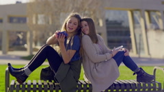 Teens Sit Back To Back, Girl Shows Her Friend Something Funny On Her Smatphone Stock Footage