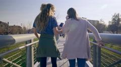 Teens Walk Across A Bridge, Girl Shares Her Headphones With Friend, They Dance Stock Footage