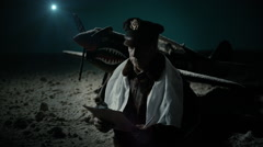 tilt to WWII Army Air Corps officer taking notes at night - stock footage