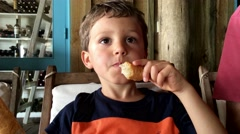 Child eating lunch. Child thinking about something. Contemplative look Stock Footage