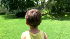 Child running outside. Young boy having fun running in outdoor sunny garden Stock Footage