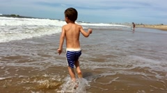 Child running at the beach. Young boy having fun at the beach Stock Footage