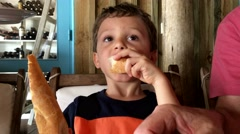Child eating bread while waiting for his meal to arrive. Close up of young boy Stock Footage