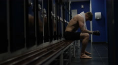 4K MMA fighter sits alone in locker room, psyching himself up before a fight - stock footage