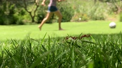 Grass. Low angle close up of grass with girl and boy playing soccer Stock Footage