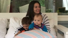 Girl sitting on a sofa with baby and young boy.  Stock Footage