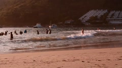 People catching some waves at sunset Stock Footage