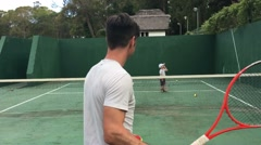 Father playing tennis with his son. Young adult teaching tennis with children. Stock Footage
