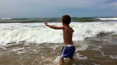 Little boy having fun at the beach enthusiastically. Child splashing and running Stock Footage