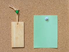 Blank wooden tag and paper on cork board Stock Photos
