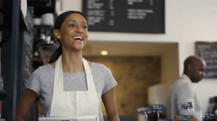 4K Cheerful worker serving a customer who uses smartphone to pay in coffee shop. - stock footage