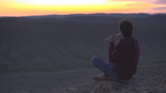 Young musician playing the flute on a desert cliff at sunset - stock footage