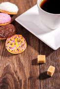 Coffee and marshmallow biscuits with icing colored granules on wood table Stock Photos