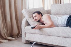 young unshaven guy lazily resting in a tracksuit - stock photo