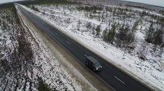 Aerial view of minivan driving winter road Stock Footage