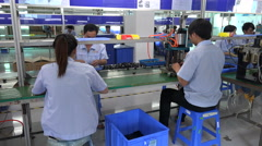 People at work on the assembly line of an electronics factory in Shenzhen, China Stock Footage