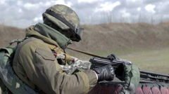 A soldier with a machine gun on a military firing range shooting at a target - stock footage