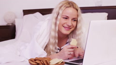 Blonde female surfing internet and eating cookies in bed Stock Footage