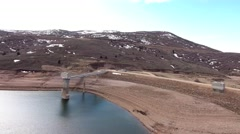 Aerial shot of a mountain dam reservoir with little water and town Stock Footage