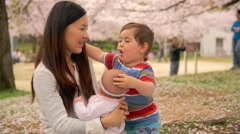 Japanese mum and mixed race children hug and embrace at the park Stock Footage