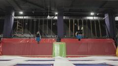 Two Professional gymnasts doing trcks on trampoline synchrone. Amazing tricks Stock Footage