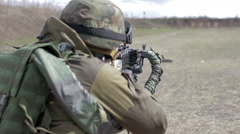 A soldier with a machine gun on a military firing range shooting at a target Arkistovideo