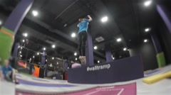 Professional Girl Gymnast doing trcks on trampoline. Flips in air. High Extreme Stock Footage