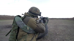 A soldier with a machine gun on a military firing range shooting at a target Stock Footage