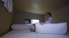 Middle aged woman lies in hotel sleepbox Stock Footage