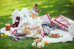 Happy child sits on a meadow around Easter decoration Stock Photos