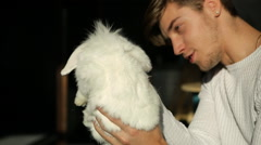 Young man and white rabbit Stock Footage