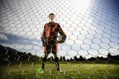A boy in a soccer shirt holding a soccer ball, standing in goal. Stock Photos