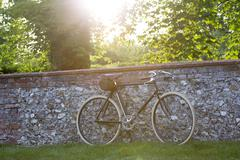 A vintage style racer bike leant against a brick and flint wall. - stock photo