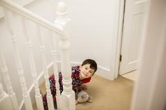 A boy sitting on the stairs, looking upwards and grinning. Stock Photos