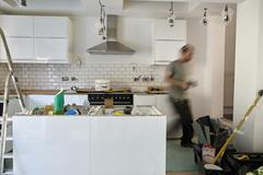 A man working in a kitchen, installing new units. Blurred motion. Stock Photos