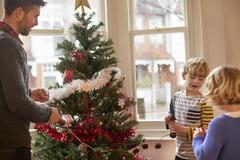 A father and two children decorating a Christmas tree at home. - stock photo