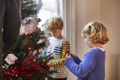 Two children decorating a Christmas Tree in a family home. - stock photo