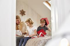 A mother and two children opening presents. Stock Photos