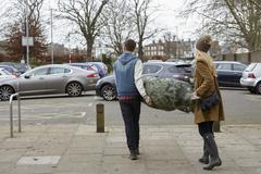 Two people carrying a netted Christmas tree to the car park. Stock Photos