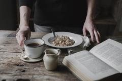 A person at a table with a cup of coffee, bowl of muesli and an open book. Stock Photos