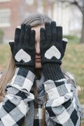 A girl wearing wooly gloves with a heart shaped design, hiding her face. - stock photo