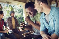 A group of friends, men and women at a house party. Two men laughing. Stock Photos