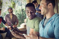 House party, two men looking at smart phones. Stock Photos